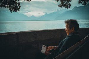 Man reading book overlooking lake